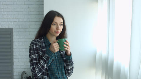 Cute woman drinking coffee and looking out window Archivo