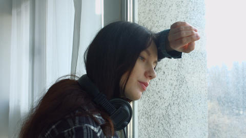Melancholic young woman leaning on window Footage