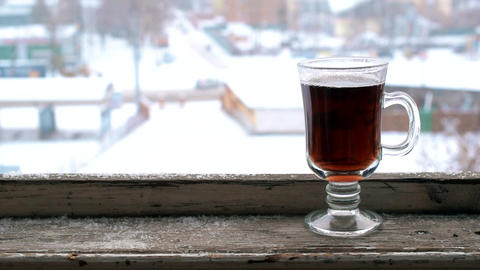 Snow falling on glass cup on old wooden window sill Footage