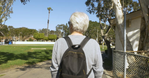Camera following a happy healthy senior man with gray hair walking through a Footage
