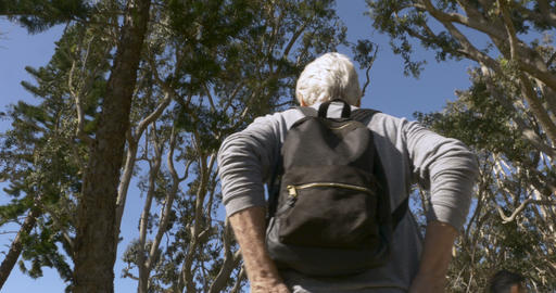 Low angle following an elderly senior man walking through a park with his hands Footage