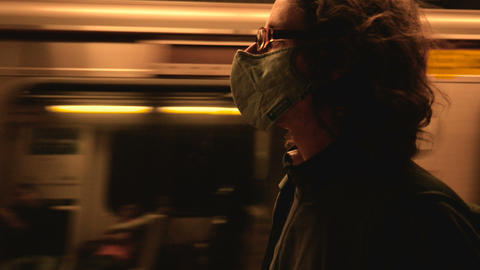 Man wearing a face mask as a moving subway train goes by in slow motion GIF