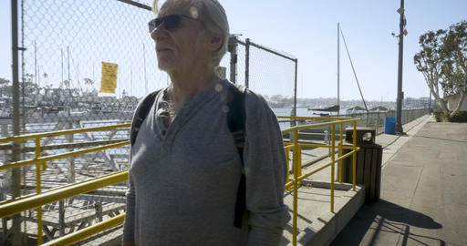 Camera follows a healthy fit elderly senior man in his 60s or 70s walking Footage
