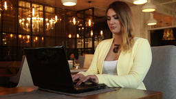 Business woman working using a mobile computer sitting at a table in a cafe.HD Footage