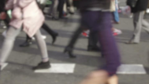 Detail of blurred feet walking toward the left in a pedestrian crossing Footage