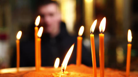 Burning candles in the foreground, man in the back out of focus Footage