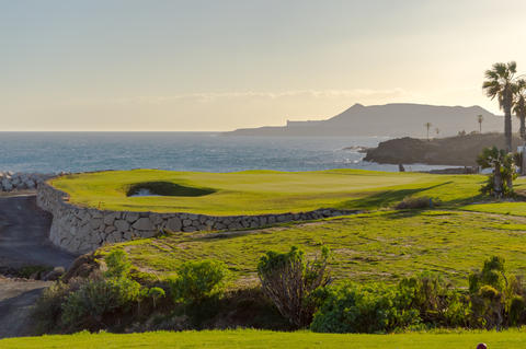 Green golf with flag and hole facing Atlantico ocean in Santa Cr フォト