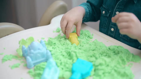 The child builds with his hands from the green kinetic sand castles and towers Footage