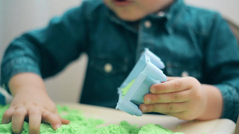 A boy in a denim shirt builds castles and various figures of green kinetic sand Footage