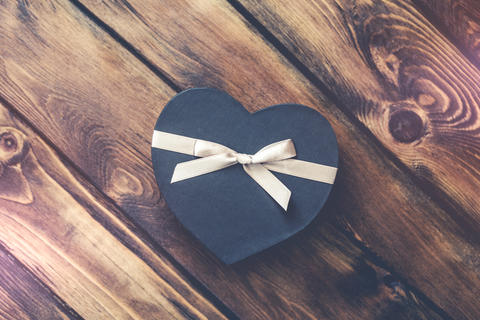 Black heart shaped gift box on old wood Photo