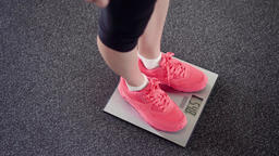 Girl measuring her weight on electronic scales. Slim female legs in pink Footage