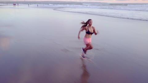 Aerial tracking pan Asian woman running on sunset beach Archivo