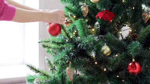 woman decorating christmas tree with ball Footage