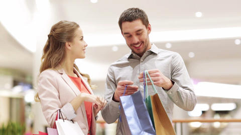 happy young couple with shopping bags in mall Footage