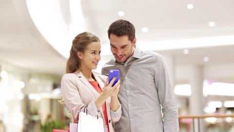 couple with smartphone and shopping bags in mall Footage