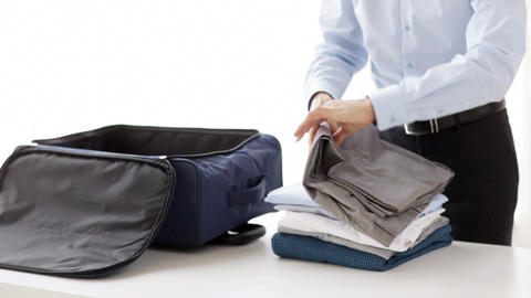 businessman packing clothes into travel bag Archivo