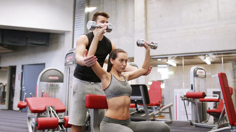 young couple with dumbbells flexing muscles in gym Footage