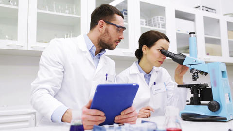 scientists with tablet pc and microscope in lab Footage