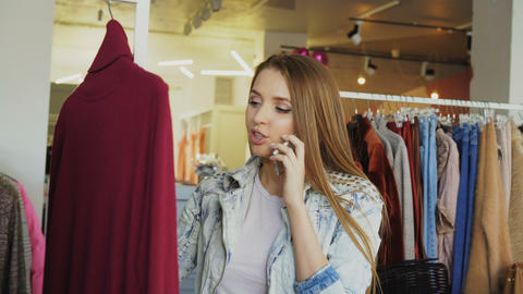 Young woman talking on mobile phone and choosing clothes in boutique. She is Footage