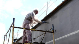 Worker paints with brush metal front of ship at shipyard in port of Moscow Footage