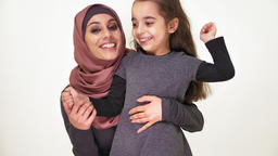 Young beautiful mother in hijab hugs her little daughter, laughing family, happy Footage