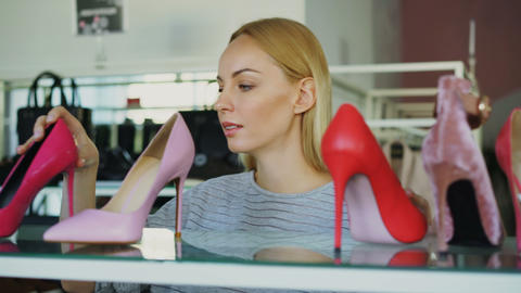 Close-up shot of blond young woman choosing high-heel shoes in footwear store Live Action