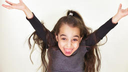 Little beautiful sweet girl is happy, smiling, rejoicing, raises her arms to the Footage
