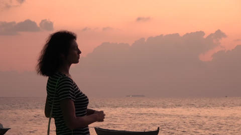 Girl is looking at a pink cloudy sky. Maldives video Archivo
