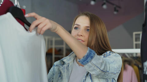 Close-up shot of attractive girl choosing clothes in boutique. She is going Footage