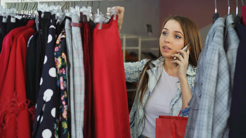 Attractive girl choosing clothes in modern shop and talking on mobile phone Footage