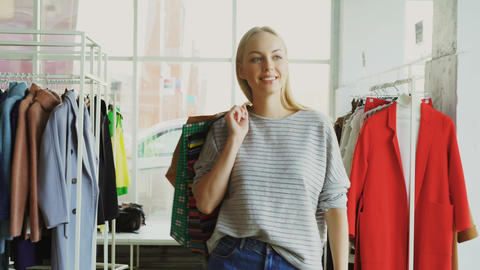 Dolly shot of blond girl walking between shelves and rails in large store. She Footage
