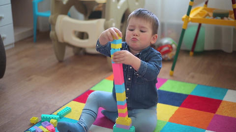 A little boy can't build a tall tower out of a constructor Footage