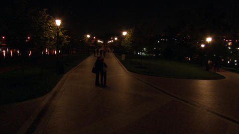People walk at night near dancing fountains Live Action