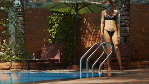 Lady in Bikini Stands up Goes to Pool Metal Stairs Footage