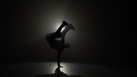 Talented young boy silhouette performing break dancing tricks in front of the Footage