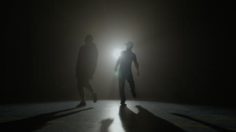 Break dancers syncron dancing choreography on a stage with dark foggy background Footage