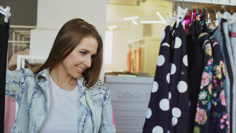 Pretty woman wearing denim is shopping for clothes, looking at trousers, jackets Footage