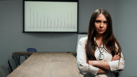 Portrait of beautiful girl in office clothes standing in conference room with Live Action