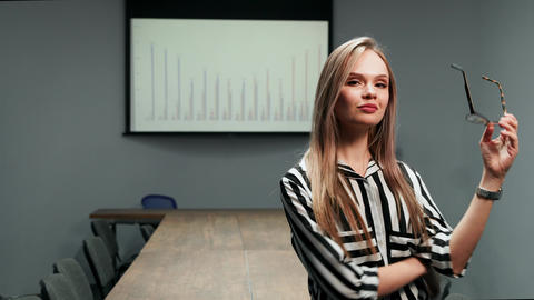 Portrait of a sexy blonde business woman in office clothes standing in the Footage