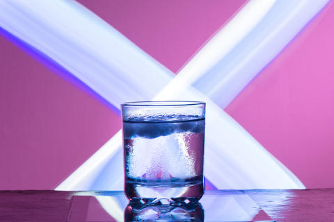 Liquid with ice in a glass on a reflective surface on a reddish background Photo
