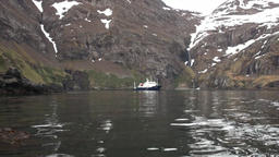 Ship near waterfall in rocky coast and mountains of Falkland Islands Footage