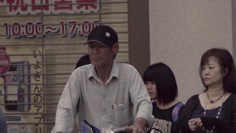 People cross an intersection in Matsuyama, Japan ビデオ