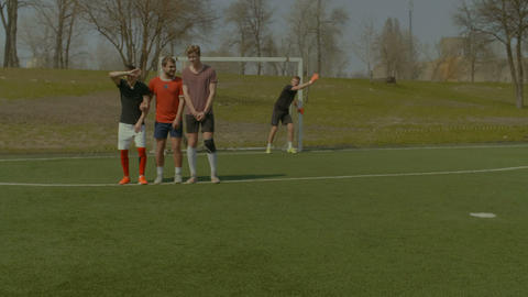 Football players forming wall to try to block ball Footage