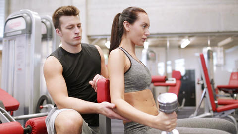 young couple with dumbbell flexing muscles in gym Footage