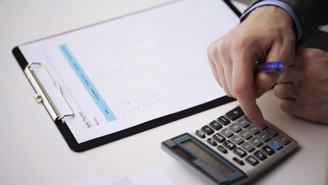 close up of businessman with papers and calculator Live Action