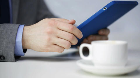 close up of man with tablet pc drinking coffee Footage