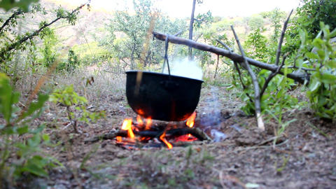 Camp life. On fire to boil pot of soup for traveler Footage