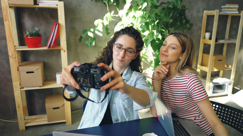 Female students are making selfie with camera while sitting together at table in Footage