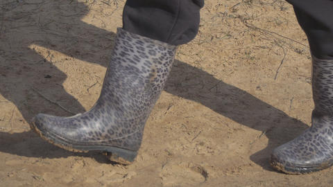 Walking in rubber boots on the sand Footage