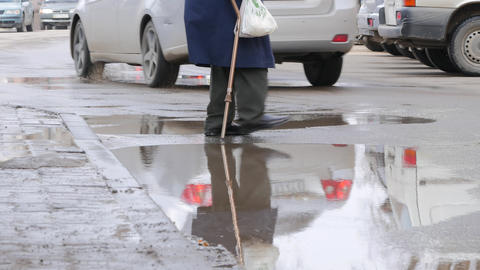 an old man with a stick cross the road Footage